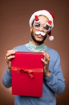 Fröhlicher junger mann aus gemischten rennen in smart casualwear, weihnachtsbrille und weihnachtsmütze mit roter geschenkbox mit seinem geschenk vor der kamera