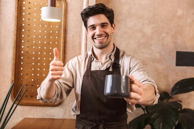Fröhlicher junger mann barista mit schürze, der im café steht, kaffeetasse zeigt und daumen hochgibt
