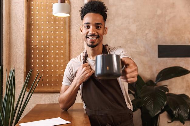 Fröhlicher junger mann barista mit schürze, der im café steht und kaffeetasse zeigt