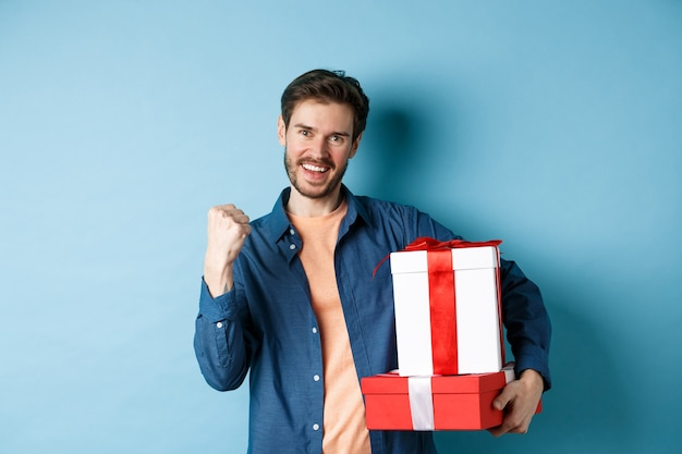 Fröhlicher junger mann bekam rabatte am valentinstag, machte faustpumpe und sagte ja, hielt geschenkboxen mit geschenken für liebhaber, die über blauem hintergrund stehen.