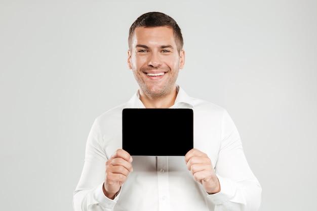 Fröhlicher junger mann, der anzeige des tablet-computers zeigt.