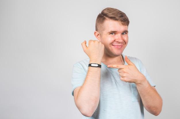 Fröhlicher junger mann, der auf fitness-tracker über grau steht und zeigt