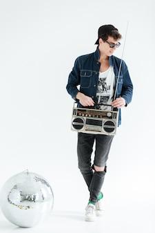 Fröhlicher junger mann, der boombox nahe discokugel hält.
