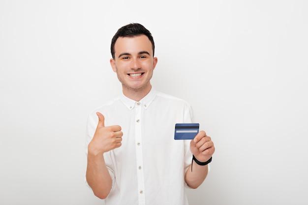 Fröhlicher junger mann, der daumen oben geste zeigt und mit einer anderen hand eine kreditkarte auf weißem hintergrund hält