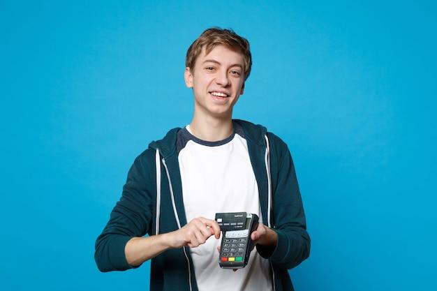 Fröhlicher junger mann, der ein drahtloses modernes bankzahlungsterminal hält, um kreditkartenzahlungen einzeln auf blauer wand zu verarbeiten und zu erwerben. menschen aufrichtige emotionen, lifestyle-konzept.