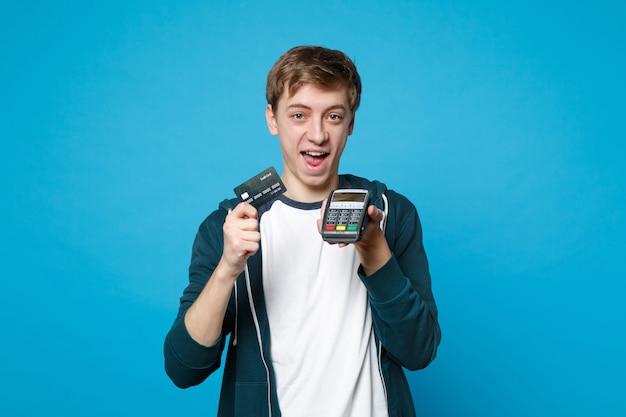 Fröhlicher junger mann, der ein drahtloses modernes bankzahlungsterminal hält, um kreditkartenzahlungen einzeln auf blauer wand zu verarbeiten und zu erwerben. menschen aufrichtige emotionen lifestyle-konzept.