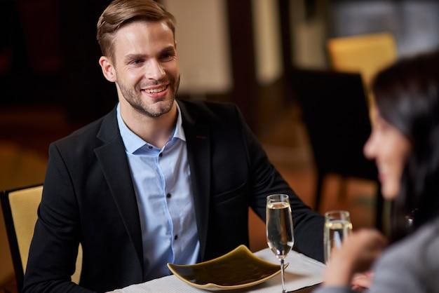 Fröhlicher junger mann, der ein restaurant-date mit einer frau hat
