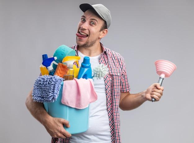 Fröhlicher junger mann, der eine kappe trägt, die einen eimer mit reinigungswerkzeugen mit einem kolben hält, der die zunge isoliert auf weißem hintergrund zeigt