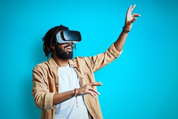 Fröhlicher junger mann, der eine virtual-reality-brille trägt, während er gegen die blaue wand steht