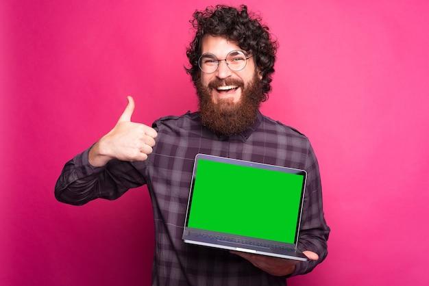 Fröhlicher junger mann, der einen daumen und einen computer hochhält