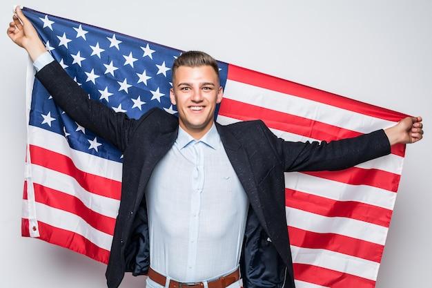 Fröhlicher junger mann, der flagge von grau der vereinigten staaten hält
