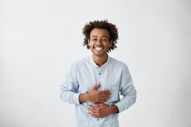 Fröhlicher junger mann, der hände auf bauch hält, während er über etwas lustiges laut lacht