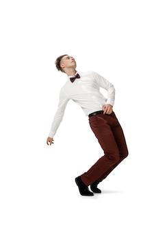 Fröhlicher junger mann, der in freizeitkleidung oder anzug tanzt, der legendäre bewegungen der berühmtheit neu macht