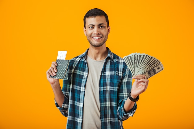 Fröhlicher junger mann, der kariertes hemd trägt, das lokal über orange hintergrund steht, geldbanknoten hält und pass mit flugtickets zeigt