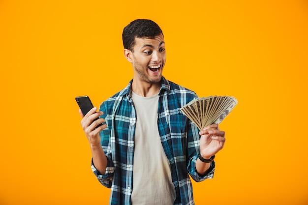 Fröhlicher junger mann, der kariertes hemd trägt, das lokal über orange hintergrund steht, unter verwendung des mobiltelefons, das geldbanknoten zeigt
