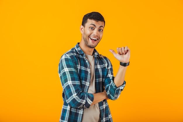 Fröhlicher junger mann, der kariertes hemd trägt, das lokal über orange wand steht und finger auf sich selbst zeigt