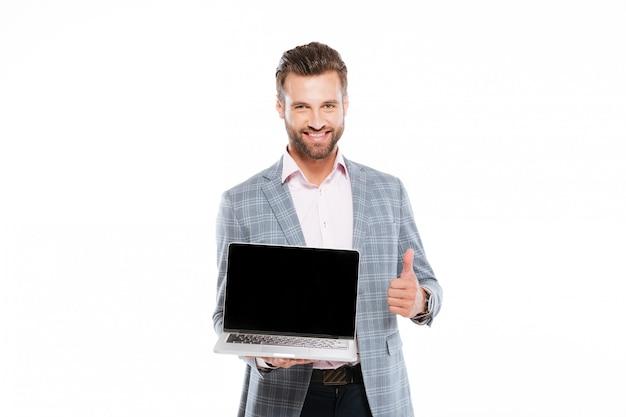 Fröhlicher junger mann, der laptop hält, der daumen oben zeigt.