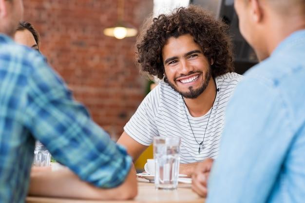 Fröhlicher junger mann, der mit freunden im café sitzt
