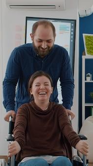 Fröhlicher junger mann, der mit seinem behinderten, gelähmten, ungültigen mitarbeiter rollstuhl schiebt, während er im finanzbüro lächelt. kollegen haben spaß am lachen am arbeitsplatz während der arbeitszeit