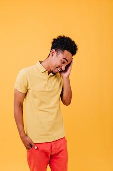 Fröhlicher junger mann, der nach unten schaut. trendy afrikanischer kerl, der mit überraschtem lächeln aufwirft.