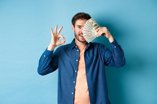 Fröhlicher junger mann, der ok-zeichen zeigt und hälfte des gesichts mit dollar bedeckt, auf blauem hintergrund stehend.
