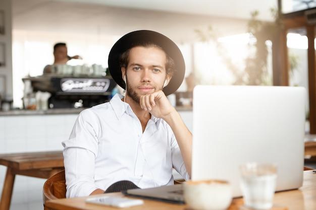 Fröhlicher junger mann, der pause im kaffeehaus hat, mit elektronischen geräten am tisch sitzt und musik online auf kopfhörern genießt