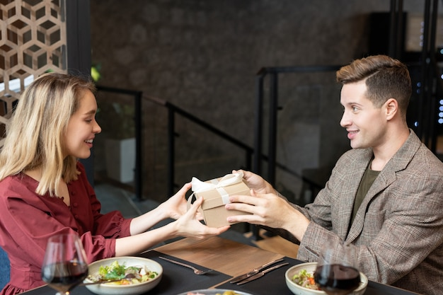 Fröhlicher junger mann, der seiner hübschen freundin eine geschenkbox mit geschenk zum valentinstag übergibt, während er beide am servierten tisch sitzt und zu abend isst
