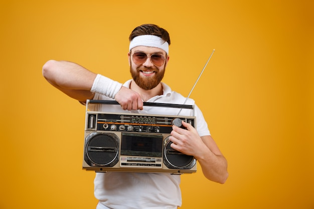 Fröhlicher junger mann, der sonnenbrille hält, die tonbandgerät hält