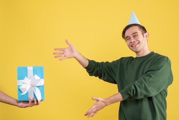 Fröhlicher junger mann der vorderansicht, der auf das geschenk in der menschlichen hand auf gelb zeigt