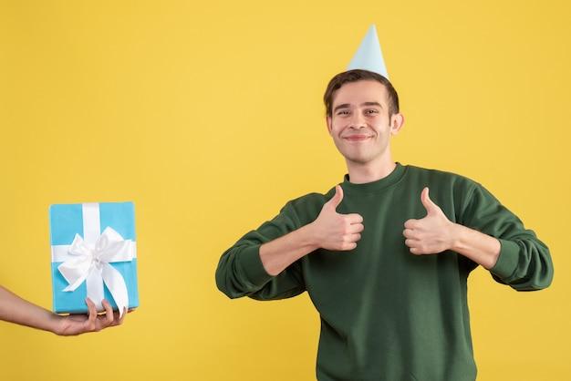 Fröhlicher junger mann der vorderansicht, der das geschenk des daumen hoch in der menschlichen hand auf gelb macht