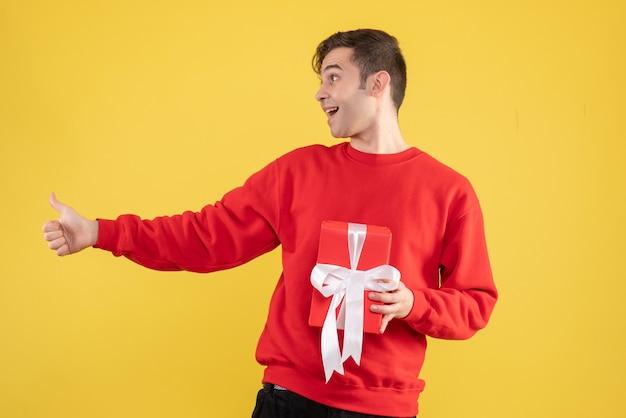 Fröhlicher junger mann der vorderansicht mit dem roten pullover, der daumen auf zeichen gelb macht