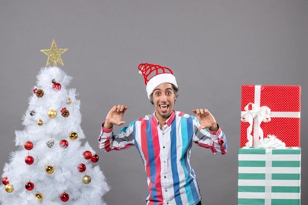 Fröhlicher junger mann der vorderansicht mit geöffneten händen, die nahe weißem weihnachtsbaum stehen