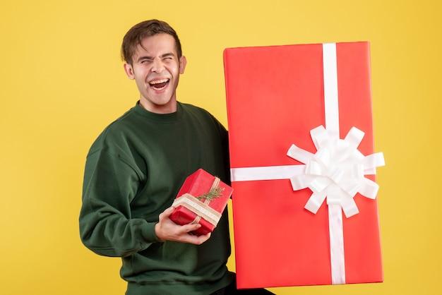 Fröhlicher junger mann der vorderansicht mit grünem pullover, der große und kleine geschenke hält, die auf gelb stehen