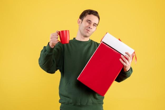 Fröhlicher junger mann der vorderansicht mit grünem pullover, der großes geschenk und rote tasse hält auf gelb hält