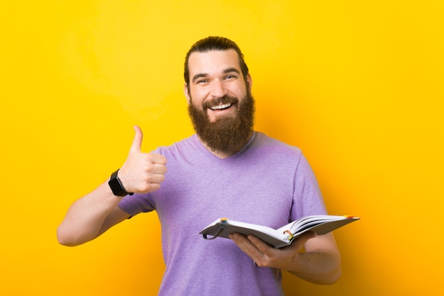 Fröhlicher junger mann empfiehlt zu schreiben, während er den daumen zeigt.