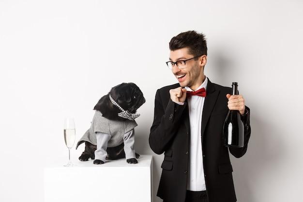 Fröhlicher junger mann im anzug, der neujahr mit haustier, hund und mann feiert, der sich ansieht, besitzer trinkt champagner und steht auf weißem hintergrund.