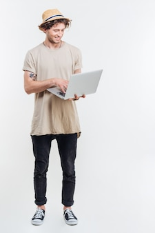 Fröhlicher junger mann im hut stehend und unter verwendung des laptops über weißem hintergrund