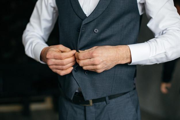 Fröhlicher junger mann in einem grauen anzug berührt eine jacke