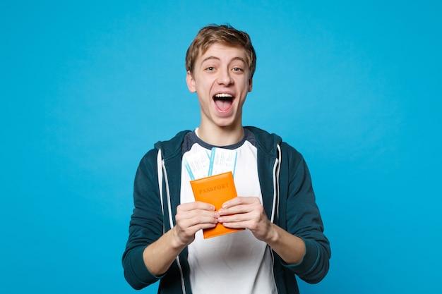 Fröhlicher junger mann in freizeitkleidung, der den mund weit offen hält, reisepass hält, bordkarte einzeln auf blauer wandwand. menschen aufrichtige emotionen, lifestyle-konzept.