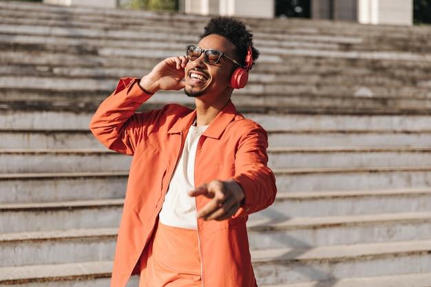 Fröhlicher junger mann in orangefarbener jacke, buntem t-shirt und sonnenbrille singt, tanzt und hört musik über kopfhörer draußen