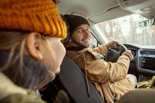 Fröhlicher junger mann in warmer winterkleidung, der seine süße kleine tochter mit einem zahnigen lächeln ansieht, während er am steuer sitzt und zum landhaus fährt