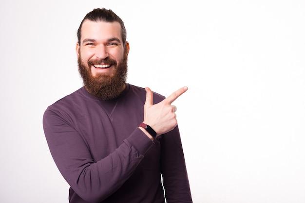 Fröhlicher junger mann lächelt in die kamera und zeigt mit einem finger weg auf einen freien raum neae eine weiße wand
