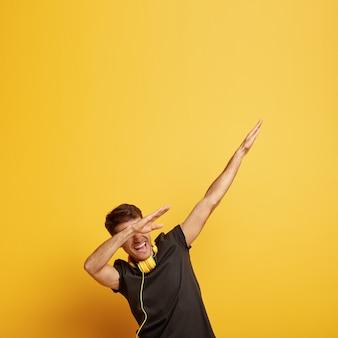 Fröhlicher junger mann macht tupfen tanzgeste, zeigt tupfen bewegung