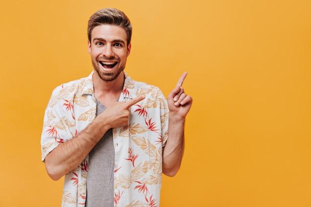 Fröhlicher junger mann mit bart in modernem weißem hemd und grauem t-shirt, der zwei finger zum platzieren für text zeigt und auf oranger wand lächelt