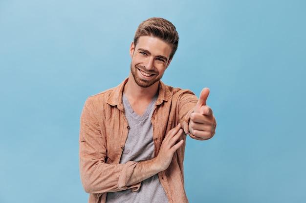 Fröhlicher junger mann mit bart in modischem outfit, der seinen finger an einer isolierten blauen wand in die kamera zeigt und zeigt