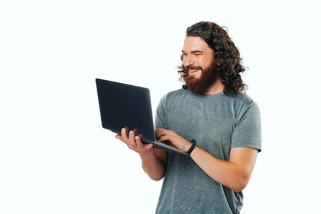 Fröhlicher junger mann mit bart lächelnd und mit laptop auf weißem hintergrund