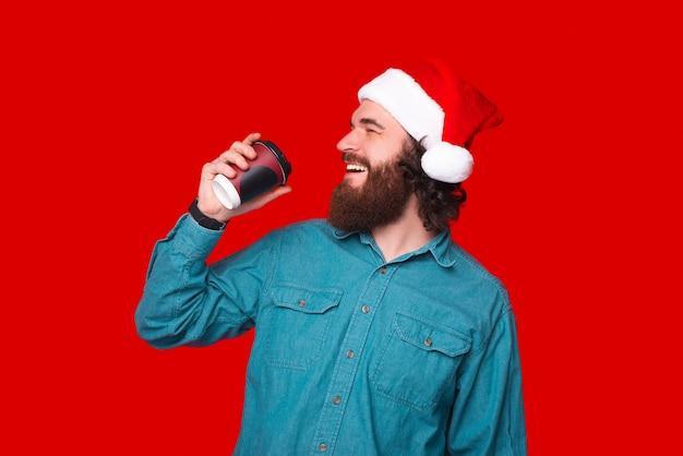 Fröhlicher junger mann mit bart trinkt eine tasse kaffee zum mitnehmen und trägt weihnachtsmann-mütze