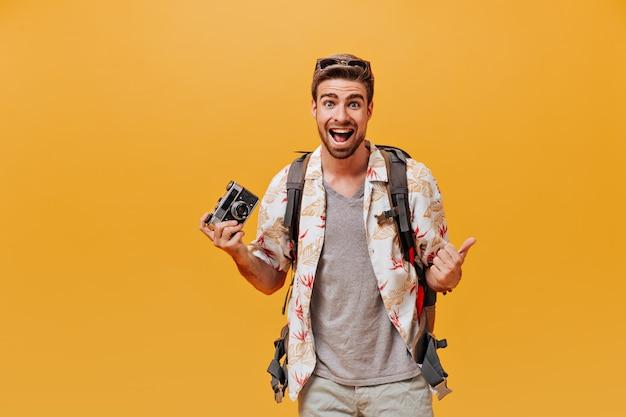 Fröhlicher junger mann mit bart und sonnenbrille in grauem t-shirt und weißem bedrucktem hemd mit blick in die kamera auf isolierter orangefarbener wand looking