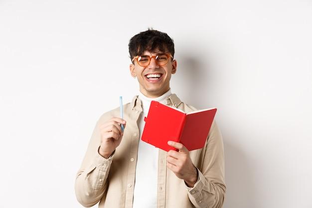 Fröhlicher junger mann mit brille, der lacht und notizen macht, im planer aufschreibt, stift und tagebuch hält und auf weißem hintergrund steht.