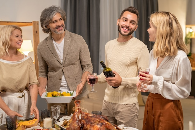 Fröhlicher junger mann mit flasche und glas rotwein, der seine frau mit einem zahnigen lächeln anschaut, während er sich am servierten tisch unter den eltern aufheitert